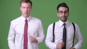 Two young multi-ethnic businessmen working together against green background. Studio shot of young handsome bearded Persian businessman and young handsome stock footage