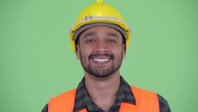 Face of happy young bearded Persian man construction worker smiling