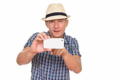 Studio shot of young handsome Caucasian man taking picture with. Mobile phone isolated against white background royalty free stock images