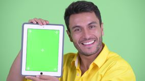 Face of happy young Hispanic businessman showing digital tablet. Studio shot young handsome Hispanic businessman against chroma key with green background stock footage