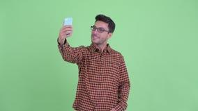 Happy young Hispanic hipster man taking selfie