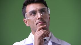 Young handsome Hispanic man doctor against green background. Studio shot of young handsome Hispanic man doctor against chroma key with green background stock footage