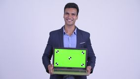 Happy young Indian businessman showing laptop. Studio shot of young handsome Indian businessman wearing suit against white background stock video footage