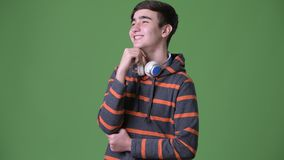 Young handsome Iranian teenage boy against green background. Studio shot of young handsome Iranian teenage boy against chroma key with green background stock footage