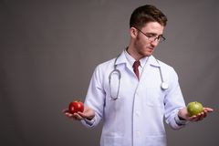 Young handsome man doctor wearing eyeglasses against gray backgr stock photos