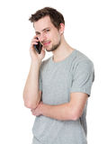 Studio shot of a young handsome man at the phone Royalty Free Stock Photos