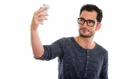 Studio shot of young handsome man taking selfie picture with mob. Ile phone while wearing eyeglasses stock photos