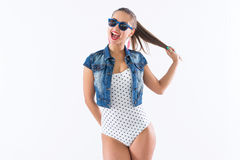 Studio shot of a young happy girl laughing, holding her hair, imitating tails hairstyle, wearing sunglasses and trendy Stock Photos