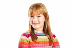 Studio shot of young little 9-10 year old girl. Wearing colorful pullover, white background stock image