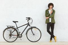 Studio shot of young male with curly hair, dressed in fashionable anorak, points with index finger at bicycle, advertises new royalty free stock photos