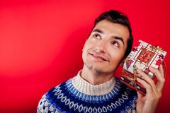 Studio shot of a young man in Icelandic sweater holding a gift box. Christmas or New Year celebration concept. Studio shot of a young man in Icelandic sweater stock photography