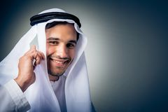 Young Man Wearing Traditional Arabic Clothing. Studio shot of young man wearing traditional arabic clothing, talking on the phone Royalty Free Stock Images