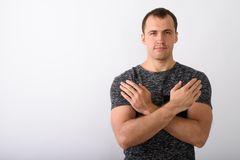 Studio shot of young muscular man with both arms crossed on ches. T against white background stock photography