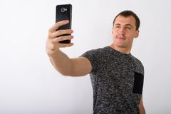Studio shot of young muscular man taking selfie picture with mob. Ile phone against white background royalty free stock image