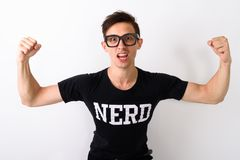 Studio shot of young nerd man flexing both arms while wearing ey. Eglasses against white background stock photo