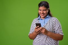 Young overweight beautiful Indian businesswoman against green background royalty free stock images