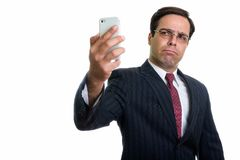 Studio shot of young Persian businessman taking selfie picture w. Ith mobile phone isolated against white background stock images