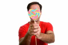 Studio shot of young Persian man covering face with delicious he. Art shaped colorful spiral lollipop isolated against white background stock photos