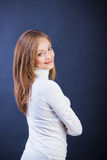 Studio shot of young smiling woman. Studio shot of young caucasian smiling woman standing sidewise with crossed arms Stock Images