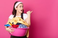Studio shot of young woman housewife with pink basin, ready for washing things, wears hair band, casual t shirt, brown apron, royalty free stock image
