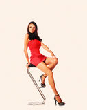 Studio shot of young woman sitting on bar stool. In red dress Royalty Free Stock Photography