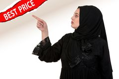 Studio shot of young woman wearing traditional arabic clothing. she`s holding her hand to the side.  Royalty Free Stock Images