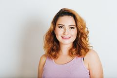 Studio shot of young 20-25 year old woman. Bright red hair, pink lipstick stock image