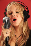 In the studio singing into old micriophone Stock Photo