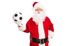Studio som skjutas av Santa Claus som rymmer en fotboll Royaltyfria Bilder