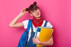Studio sparato dei camici d'uso sorridenti del denim della bella scolara, maglietta bianca, bandana, tocchi il suo mazzo Studente fotografie stock libere da diritti