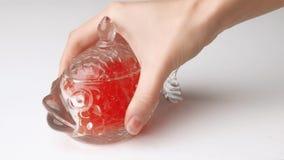 Studio sparato della mano femminile che mette barattolo di vetro in pieno del caviale rosso sulla tavola stock footage