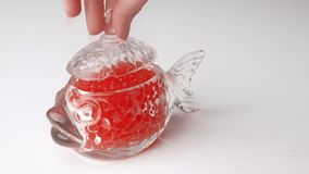 Studio sparato della mano femminile che prende caviale rosso con il cucchiaio dal barattolo di vetro nella forma di pesce archivi video