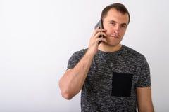 Studio sparato di giovane uomo muscolare che parla sui agains del telefono cellulare fotografia stock libera da diritti