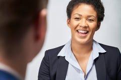 Studio sparato di occupazione di Interviewing Businessman For della donna di affari contro fondo bianco immagine stock libera da diritti