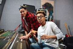 Studio staff. Man with pizza and drink and his colleague spending working day in sound recording studio Stock Image
