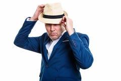 Studio strzał dojrzały biznesmena naprawiania kapelusz z oba rękami fotografia royalty free