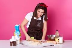 Studio strzał gniewna gospodyni domowa ubierający kuchenny fartuch brudny z mąką, t koszula, czerwona kapitałka, trzyma tocz obrazy stock