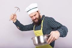 Studio strzał gniewny brodaty szef kuchni trzyma kopyść i garnek Fotografia Stock