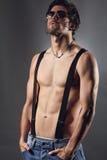 Studio strzał seksowny mężczyzna z czarnymi okularami przeciwsłonecznymi i suspenders Obraz Royalty Free