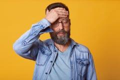 Studio strzał sprężający brodaty młody człowiek dotyka czoło, ubierającego drelich, szarą t koszula i szkła migrenę mieć, stojaki obraz stock