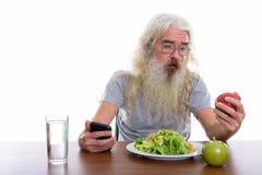 Studio strzał starszy brodaty mężczyzna mienia telefon komórkowy podczas gdy kibel zdjęcie royalty free