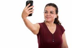 Studio strzał szczęśliwa dojrzała Perska kobieta ono uśmiecha się podczas gdy brać s zdjęcia stock