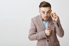 Studio strzelał śmieszny nerdy męski urzędnik patrzeje spod szkieł dotykać w modnej kurtce z modną fryzurą obraz royalty free