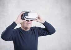 Studio strzelał senior używa VR słuchawki na szarym tle fotografia stock