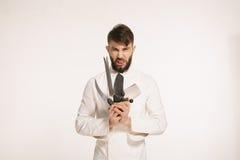 Studio strzelał szczęśliwy brodaty młody szef kuchni trzyma ostrych noże nad białym tłem Szef kuchni z nożem Przystojny gniewny p Fotografia Royalty Free