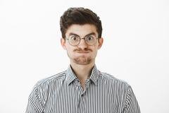 Studio strzelający śmieszny europejski facet z wąsa i choroby brwiami w modnych szkłach, robić twarzy i być dziecięcy Zdjęcia Stock