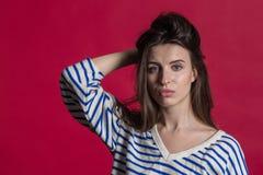 Studio tiré d'une belle belle femme d'isolement contre un mur rouge vide de studio photo libre de droits