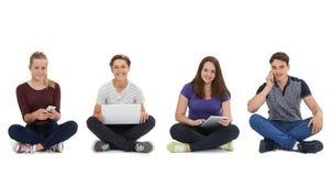 Studio tiré des adolescents employant la technologie des communications Photographie stock