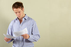 Studio tiré du jeune homme regardant des factures image stock