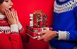 Studio van een paar in Ijslandse sweaters wordt geschoten die Mens die zijn dozen van de meisjegift geven Kerstmis of het Nieuwe  Stock Foto's